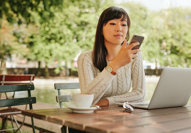 attractive-woman-using-smartphone-at-coffee-shop-PJJX2ZG